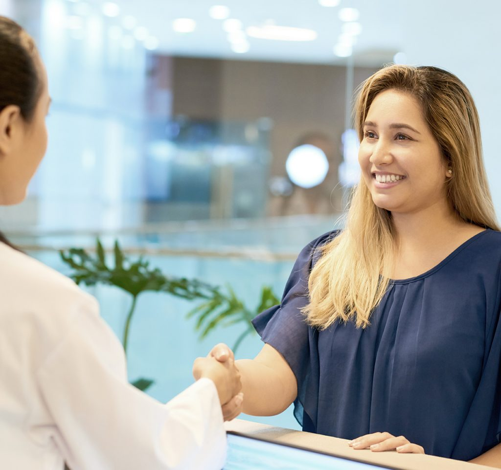 Smiling young woman shaking hand of doctor standing at reception